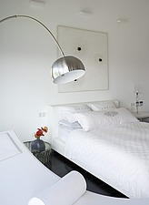 Modern white bedroom with arc light suspended above white chaise longue - 12541-260-1