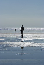 Three of the 100 iron men at Crosby Beach as part of Anthony Gormley's Another Place, Liverpool, Merseyside, England - 12790-160-1