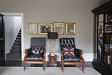 Pair of black leather button backed Victorian chairs beneath a row of gilt framed paintings - 13289-380-1