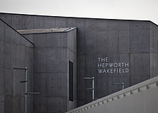 Closeup view of the front elevation and sign over the entrance of The Hepworth Wakefield with the edge of the pedestrian bridge over the River Calder... - 13298-60-1