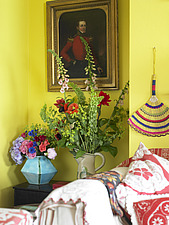 Corner of yellow sitting room with 2 vases of colourful flowers beneath a Victorian portrait of a man in red military uniform - 13412-30-1