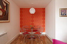 Modern furnished dining area in front of bright orange wallpaper Great Suffolk Street - 13414-70-1