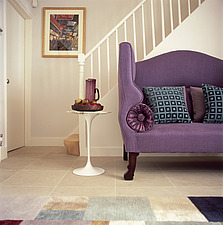 A detail of a modern, open plan staircase with banister, a small side table, a purple sofa with cushions - 26051-210-1
