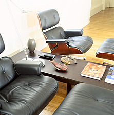 Pair of leather Eames chairs either side of wooden table in modern room - 26051-2680-1