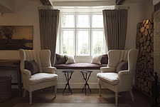 Pair of wingback chairs in front of window seat, with logs piled up in corner Barnsley House Hotel, Barnsley, Cotswolds - 13421-100-1