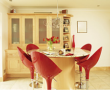 Breakfast bar with red stools in centre of kitchen - 27230-820-1