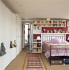 Bedroom with built in wardrobes and shelving around an iron framed bed with patchwork bed cover - 13438-170-1