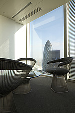 Modern metal framed chairs and coffee table by a full height window with view of the Gherkin - 13533-110-1