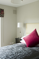 Bedroom with bed and covered headboard, red cushion, bedside lamps and window blind,  - 13551-120-1