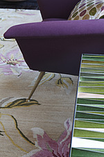 Detail of 50s purple armchair and patterned ceramic topped side-table sitting on floral rug - 13552-220-1