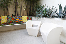 Landscape shot of 2 Ron Arad chairs in tropical courtyard garden, next to bench with African tribal print cushions - 13552-70-1