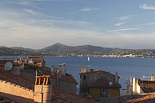 View over rooftops of St Tropez, with a yacht sailing across the bay and hills on the other side  - 13646-520-1