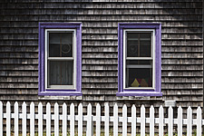 Shingles of a Carpenter Gothic cottage with white picket fence and purple window frames - 13794-340-1