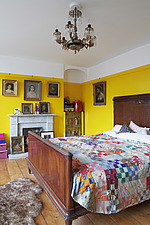 Bedroom with bright yellow walls dominated by Edwardian mahogany bed with patchwork quilt - 14200-270-1