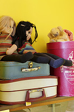 Vintage rag dolls sitting on vintage suitcases against yellow wall - 14200-280-1
