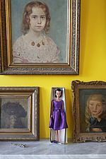 Lilli doll in 1950s style purple silk dress on mantelpiece surrounded by gilt framed portraits on bright yellow wall - 14200-310-1