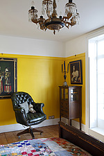Green leather button backed swivel chair in corner of yellow bedroom with small mahogany display cabinet - 14200-330-1