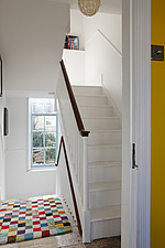 Colourful chequered rug on landing with white painted staircase outside yellow bedroom - 14200-350-1