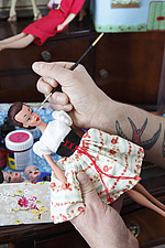 Close up of Julian painting the face of a Lilli doll wearing a dirndl style dress - 14200-440-1