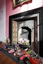 Victorian tiled fireplace in pink bathroom with African tribal masks lying on the hearth - 14200-510-1