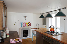 Kitchen with 1930s tiled fireplace above which letter shapes spell TOYS - 14200-540-1