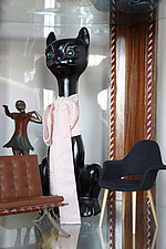 Ceramic black cat with pink bow, 1920s dancer, and miniature modernist chairs in display cabinet - 14200-80-1
