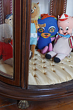 Vintage toys sitting on satin buttoned base of mahogany display cabinet, including Porky Pig - 14200-90-1