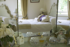 Traditional bedroom with double bed, white bedspread, reflected in dressing table mirror - 14588-400-1
