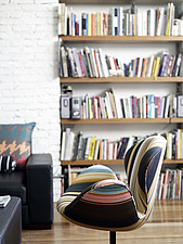 Close up of striped modern chair in front of bookcase in Brazilian residential home - 14268-210-1