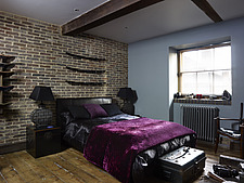 Double bed with velvet throw in brick wall bedroom of Corbetts Wharf apartment, UK - 14746-280-1