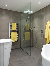 Glass divider and towel rail with yellow towels in bath and shower room in Cherry Orchard home, UK - 14751-490-1