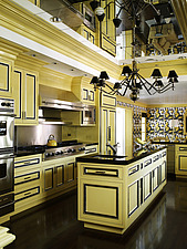 Chandelier hanging from mirrored ceiling above island unit in yellow and black kitchen in residential home, California, USA - 14349-370-1