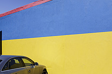 A car parked in front of a blue, yellow and red facade - 15156-290-1