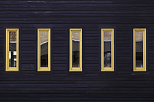 Five thin yellow windows on a dark blue clapboard wall - 15157-10-1