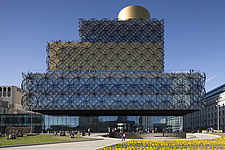 Viewed from a distance over a flowery pedestrian precinct full of people, The Library of Birmingham, with the walls that look to be covered in mesh, a... - 15853-60-1