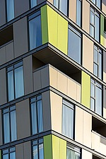 Patterns of windows, balconies and  acid yellow cladding on a  13-storey residential development in Wembley London UK - 16416-320-1