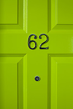 Green panelled door detail with security spy hole underneath the number 62, Bristol, England - 16417-200-1