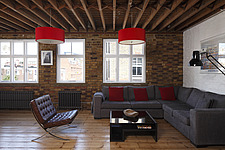 Warehouse style living room with brick walls and exposed timber ceiling, furnished with grey corner sofa and Barcelona chair   Clerkenwell loft apartm... - 16611-350-1