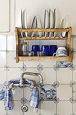 Close up of traditional style kitchen with blue and white tiles, taps and  rustic plate drying rack in a Mediterranean home - 16714-10-1