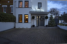 Exterior view of residential building with white and silver Christmas decorations, dusk - 16753-290-1