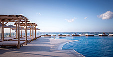 Outdoor pool view and custom-made furniture of Rinela Restaurant at Mitsis Rinela Beach Resort & Spa in Crete island Greece by Elastic Architects - 16946-110