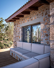 Close up of north-east facade and built-in lounge, Mayia Cottage renovation in Aigialeia Hills Peloponnese  - 16953-270