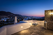 Exterior view of roof terrace and lounge at dusk overlookong Parikia bay, holiday house on Paros Island Greece by Nikolas Kouretas - ARC100454
