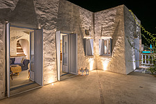 Exterior view main house terrace and stucco walls lit at night, Villa Elxis in Paros Island Greece by Studio 265 / Vazaios Petropoulos - ARC100825