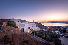 Exterior general context view of complex overlooking Naousa Bay and Mycenaean Acropolis sculptural rocks at dawn, Villa Elxis in Paros Island Greece b... - ARC100833