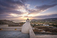 Master bedroom terrace and chimney overlooking Naousa Bay and Mycenaean Acropolis sculptured rocks at sunrise, Villa Elxis in Paros Island Greece by S... - ARC100845