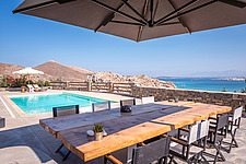 Pool terrace and custom made monastic dining overlooking Naousa Bay and Mycenaean Acropolis sculptured rocks at day, Villa Elxis in Paros Island Greec... - ARC100858