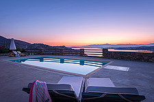 Pool terrace overlooking Naousa Bay and Mycenaean Acropolis sculptured rocks at dawn, Villa Elxis in Paros Island Greece by Studio 265 / Vazaios Petro... - ARC100859