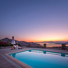 Pool terrace overlooking Naousa Bay and Mycenaean Acropolis sculptured rocks at dawn, Villa Elxis in Paros Island Greece by Studio 265 / Vazaios Petro... - ARC100860