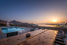 Pool terrace and custom made monastic dining overlooking Naousa Bay and Mycenaean Acropolis sculptured rocks at sunrise, Villa Elxis in Paros Island G... - ARC100863